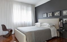 Simples, o quarto desenhado pelos arquitetos Marco Donini e Francisco Zelesnikar, do escritório Arqdonini, tem parede cinza e quadrinhos com fotos em preto e branco
