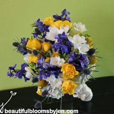 Bridal bouquet of white hydrangea, craspedia, blue delphinium,  yellow spray roses, white freesia and blue thistle by Beautiful Blooms by Je...