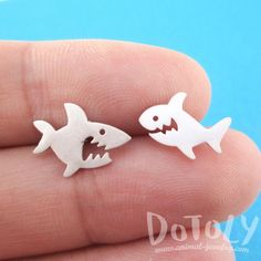 A pair of adorable shark shaped stud earrings in silver! They are slightly different for some variety, they look super cute! For more sea creature themed animal jewelry just visit our store! Store FAQ | Shipping Info | Returns & Exchanges Size: Each one measures 1.2 cm wide by 0.9 cm tall and comes with earring backs! Material: Silver Plated Tin Alloy
