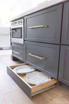 A push on the toekick with your foot reveals a hidden toekick drawer with shallow storage space for trays and other large, hard to store kitchen items! #kitchendrawer #kitchendrawers