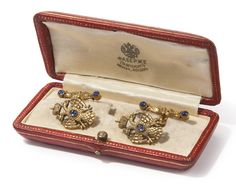 A pair of Fabergé gem-set gold cufflinks, workmaster August Hollming, St. Petersburg, 1908-1913, each link with terminals formed as an Imperial double-headed eagle centering a cabochon sapphire, connected by a gold-link chain to a bar chased with acanthus leaves and set with cabochon sapphires at either end.