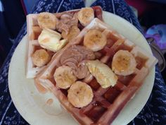 Waffles topped with banana, butter, peanut butter, and cinnamon syrup.
