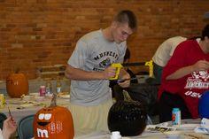 Tyler Heinonen takes a hacksaw to his pumpkin