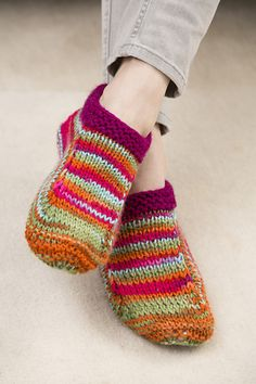 Knit these slippers in bright pretty colors and solve the cold feet problem. We used a multi-colored yarn and trimmed them with a solid, but you can choose any colors your heart desires!