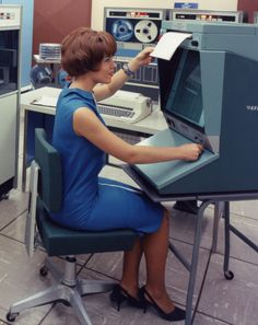 Pretty girl in blue operating a pretty blue computer, c. 1960s. | One thing I like about this photo is that she looks  happy, as if she enjoys her job and finds it suitably stimulating. (Or perhaps she's just happy to be employed as something other than an old louse's Girl Friday. Ow.) Even today, the topic of women at work is an interesting one and, I believe, would be an ideal subject for a photo-essay.