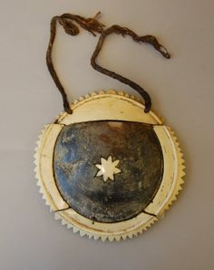 .Breast-plate worn as an ornament. The centre is a piece of black lipped pearl-shell, surrounded by four pieces of cachalot ivory attached with coconut fibre through drilled holes. The centre is decorated with a seven pointed star of cachalot ivory. Coconut fibre suspension cords.
