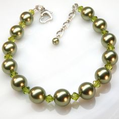 This green pearl bracelet is classic and elegant. A fantastic gift for your bridesmaids on your wedding day. Light olive or lime green Swarovski crystal pearls are combined with Swarovski crystals to create a fun autumn bracelet. The crystals add a touch of sparkle to this classic pearl bracelet. Finished with a sterling silver lobster clasp.    Great for autumn weddings, or everyday for work and play. Ask about the matching necklace or earrings to create a complete set.    Fourth photograph…