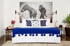 Blue and white bedroom and black and white art, flowers on bedside table and industrial wall sconces