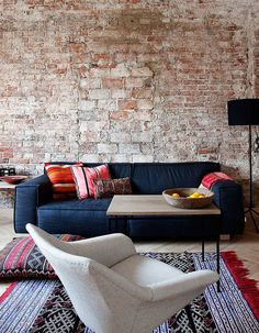 Modern rustic ethnic chic. brick wall + charcoal sofa + bright pillows #aphrochic