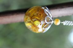 Joli collier en bulle de résine d'inclusion avec de véritables fleurs des champs cueillies et séchées par mes propres soins. Au dessus de la bulle se tiens une coupelle argentée sous forme de fleur ainsi qu'une perle jaune rayée en acrylique. Cette bulle de 2.5cm de diamètre est montée sur une chaine argentée de 80cm.
