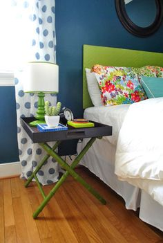 Adhesive strips can magically transform two individual pieces of furniture into one! Here, an adorable green luggage rack securely attaches to a black tray and together they become a nightstand you can actually disassemble and fold away when you need a change.