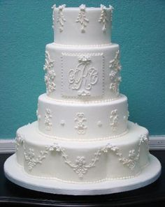 4 tier #wedding #cake with filigree and florals embellsihed with a monogram