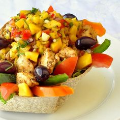 Low Fat Chicken Taco Salad with Mango Salsa - a baked whole wheat taco bowl gets filled with seasoned chicken breast and plenty of vegetables before being topped with a mango lime salsa which serves as a fat-free dressing. It's too delicious to even think about how healthy you are eating.