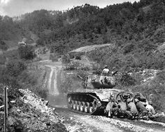 Marine infantrymen take cover behind a tank while it fires on Communist troops ahead. Hongchon Area, May 22, 1951. Sgt. John Babyak, Jr. (Marine Corps)