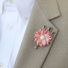 This simple and elegant mens boutonniere is handmade from satin ribbon with an ivory pearl center. The flower is 1 3/4 wide with a clutch pin