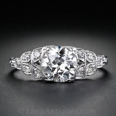 A bright white and lively 1.20 carat European-cut diamond scintillates  from an original 1920s-1930s vintage Art Deco platinum and diamond engagement ring. The graceful diamond set shoulders exhibit a classic stepped down design with light and airy open work for an extra dose of femininity. Delicate hand engraving on the top of the ring shank completes this superb and timeless antique engagement ring.