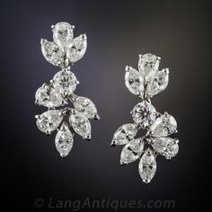 18K White Gold Diamond Cluster Earrings. A harmonious medley of bright white and beautiful marquise and pear shape diamonds, divided by one round brilliant-cut diamond, swing and sway and throw off sparks in all directions in these classic Harry Winston style drop earrings - circa mid-to-late-twentieth century. These dressy and dazzling dangles, measuring 1 inch long, are superbly crafted in gleaming 18K white gold and sparkle mightily with 5.00 carats total diamond weight.