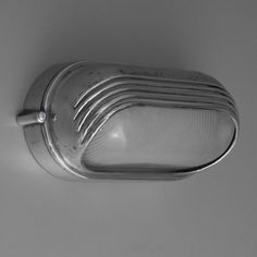 Streamlined oval nautical bulkhead lights in the Art Deco style salvaged from 1950s cruise ships.