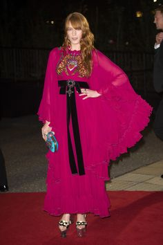 Florence Welch accompanied Gucci creative director Alessandro Michele on the red carpet to British GQ's 2016 Men of the Year Awards—where he picked up the Designer of the Year prize—in a Gucci Cruise 2017 silk cape dress with ruffles and embroidered patch detail, a silk Broadway clutch with tiger head closure and platform wedges. The musician also wore fine jewelry from the Gucci Flora collection.