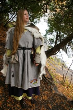 Reindeer skin cloak worn over an overdress with Celtic needlework. Under that there is the viking apron and the underdress.