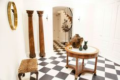 """Original black-and-white marble floors welcome guests into the home's lower-level entry, where they're greeted by a display of funky collectibles: carved wooden columns from an antiques buying trip, a leopard-print stool, and a pair of ceramic Mexican pineapples, eBay finds inspired by Berkus's own collection. """"Every time I walk up the stairs, I think, I'm so lucky to live here,"""" says Buxbaum."""