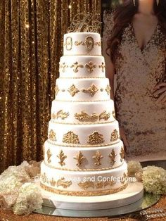White wedding cake with gold decor and gold crowns.
