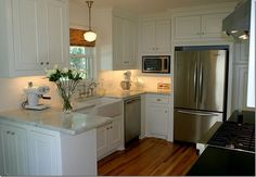 simple... white cabinets, light countertop, wood floors and stainless steel appliances.  the under-cabinet lighting looks great too