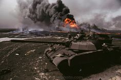 An abandoned Iraqi tank in front of the burning Magwa oil fields in Kuwait after the end of the Gulf War in 1991 (July, 1991). The desert wa...