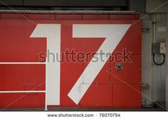 stock photo : a red japanese tsunami watertight door in osaka bay area with the number 17 painted on it