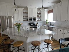 Wood shelves and barstools warm up a white kitchen. (Via TDA Decorating and Design)