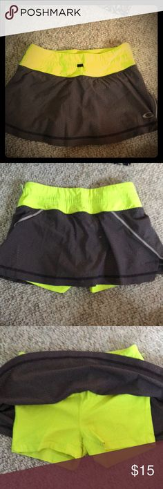 Neon yellow and grey Oakley tennis skirt Neon yellow and grey Oakley tennis skirt perfect for playing tennis or working out. Size XS. Oakley Skirts