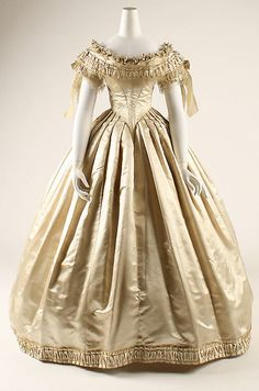 1855-62, wedding dress. As weddings at the time were in the morning, arms and neck would be covered at the wedding. Later, the sleeves would be removed to use the dress as ball dress.