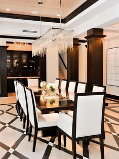 This beautiful & luxurious dining room is another variation on the black & white theme. The floor is of a geometric pattern, the stepped ceiling is enhanced with color & the sideboard & hutch  holds all your fine china. The linear chandelier is exquisite. Very chic....V