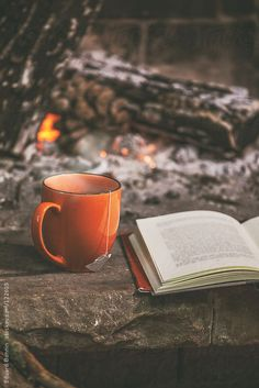 A hot cup of tea and book in a fireplace.