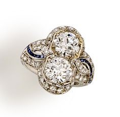 An art deco diamond two-stone ring  centering two vertically set old European-cut diamonds within a single-cut diamond surround completed by single-cut diamond and calibré-cut sapphire braided shoulders and an engraved mount; central diamonds each weighing approximately: 1.30 carats; mounted in platinum