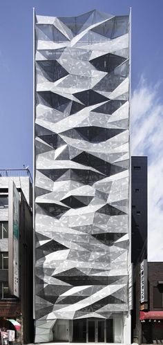 japan. Tokyo. Ginza. A folding geometric facade makes this building by japanese architecture firm Amano Design Office. Facing the back side of a the central street in Ginza. computer algorithms determined the irregular form, which reduced the need for air conditioning.