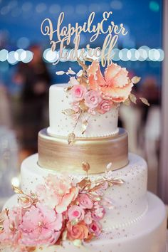 gold and white wedding cake with pink flowers and topper