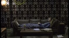 Benedict Cumberbatch as BBC Sherlock Holmes stretched out on the sofa in his blue robe.