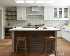 Rustic cottage kitchen features four skylights situated over a plank island topped with white marble lined with saddle stools atop a terracotta hex tile floor.