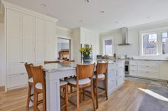 transitional kitchen idea with kitchen island extended to dining table wood chairs with comforters i shaped countertop floor to ceiling storage system in white stainless steel appliances of Tens of Inspiring Kitchen Islands with Storage and Chairs
