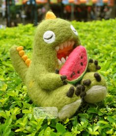 Cute little needle felted dragon eating watermelon