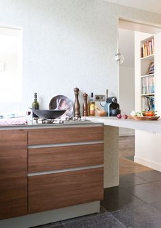 Maatwerk keuken in warm hout | donkere vloer van natuursteen | wand van wit glasmozaiek | inbouwkasten op maat...