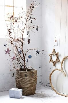 beautiful Christmas decoration corner. Love the wicker basket and the delicate stars in the tree and the rope decorations.