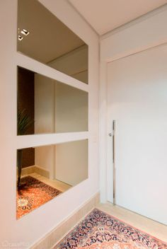 Hall social residencial. Parede revestida com papel de parede de um lado e, do outro, espelhos no tom bronze. Tapete turco, porta em laca. Projeto Rose Ferraresi.