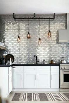 White Kitchen Cabinets . Black Counter-tops . Silver Tiles Splash-back / Hanging Edison Lights