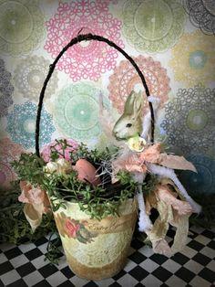 This little Easter basket is made from a peat pot. It stands 8 inches tall including the handle. The pot itself is 3 inches tall with a diameter of 3 inches. The peat pot has been painted white and antiqued with brown ink. A paper doily has been decoupaged to the front with a