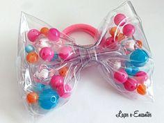 Laço feito em plastico com pedrinhas coloridas medindo em torno de 12cm.  Ideal para usar na piscina ou praia pois se molhar não estraga!