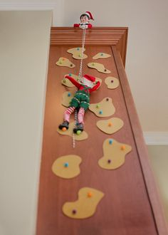 Elf on the Shelf Ideas. The elves are rock climbing up the side of our kitchen cabinets. To view more pins like this one, search for Pinterest user amywelsh18.