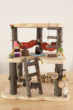 This Wooden Tree House Play set is made with all natural materials including clean dry branches and smoothly sanded pine boards. The open concept home allows for multiple children to join the fun! Bring it outside on a sunny day and encourage kids to bring nature items for imaginative play! This set includes: Treehouse- 14.5 x 11 wide and 16 tall Attached Features: two hammocks - 100% cotton, hand crocheted rope ladder mailbox two mossy toadstools Unattached Features: ladder to reach 2nd...