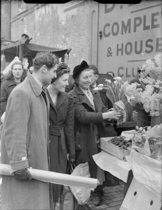 A smiling flower-seller sells flowers fresh from Covent Garden to two happy customers visiting her stall at this London market. London History, British History, Vintage London, Old London, The Blitz, London Pictures, London Photography, London Life, Covent Garden